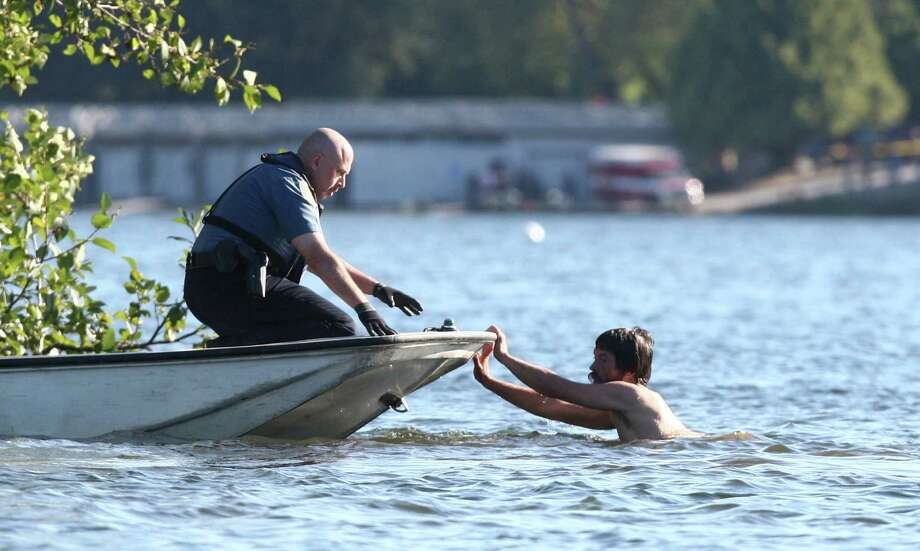 A naked man pushes on a boat with a Seattle police officer aboard as officer pursue the man. Photo: JOSHUA TRUJILLO / SEATTLEPI.COM
