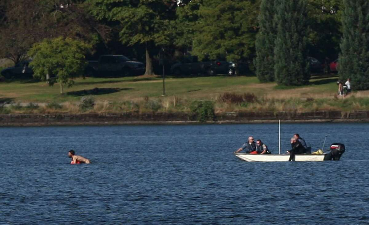 A naked man clings to a buoy as he swims from Seattle police officers after they said he assaulted two young people and was chased into the middle of Green Lake.