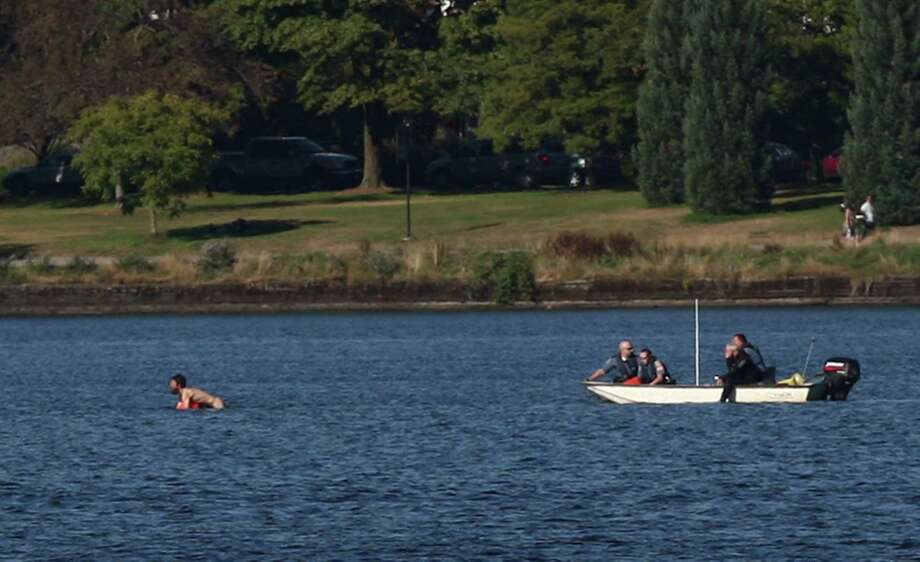A naked man clings to a buoy as he swims from Seattle police officers after they said he assaulted two young people and was chased into the middle of Green Lake. Photo: JOSHUA TRUJILLO / SEATTLEPI.COM