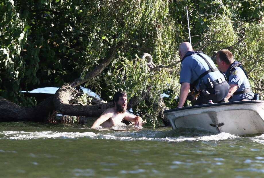 Officers pursue a naked man around Duck Island after they said he assaulted two teenagers at Green Lake Park and was chased into the middle of Green Lake. Photo: JOSHUA TRUJILLO / SEATTLEPI.COM