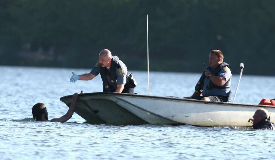 Officers try to coax a naked man onto a boat after they said he assaulted two teenagers at Green Lake Park and was chased into the middle of Green Lake. He clung naked to a buoy before swimming to Duck Island where he continued to evade police for about 2 hours. They finally arrested the man. Photo: JOSHUA TRUJILLO / SEATTLEPI.COM