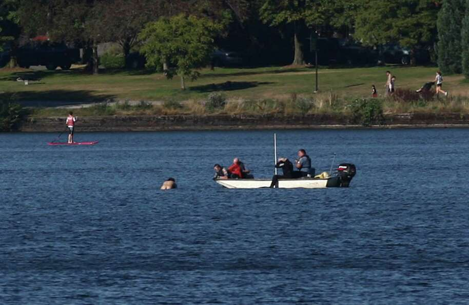 A naked man clings to a buoy as he swims from Seattle police officers 