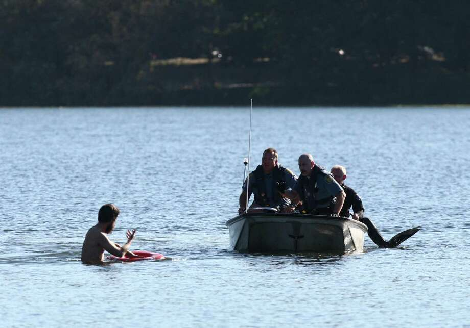 Officers try to coax a naked man onto a boat after they said he 