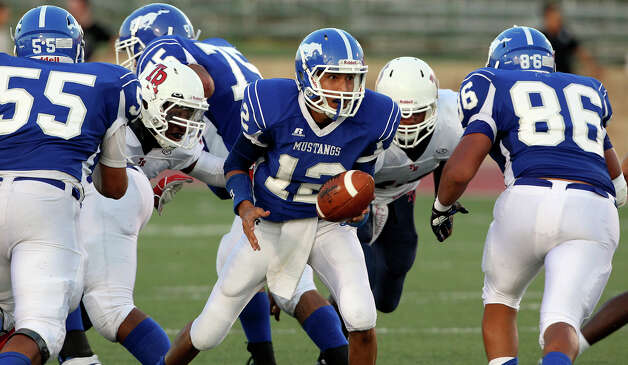 Mustang quarterback Jose Martinez turns for a handoff as Jay plays Roosevelt at Gustafson Stadium on September 6, 2012. Photo: Tom Reel, San Antonio Express-News / ©2012 San Antono Express-News
