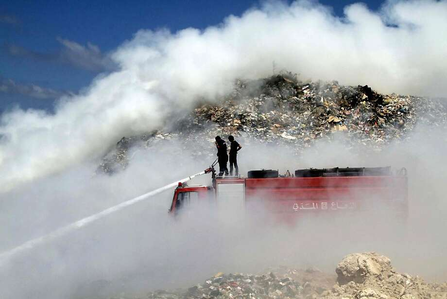 Lebanese firefighters try to extinguish a fire in southern port city of Sidon, Lebanon, Thursday, Sept. 6, 2012. A huge fire that erupted in Sidon's landfill on Thursday, which was caused by methane gas leakage, forced the industrial sector to shutdown due to  plumes of smoke and toxic fumes that will require at least 48 hours to extinguish, a source at the Civil Defense Department said. Photo: Mohammed Zaatari, Associated Press
