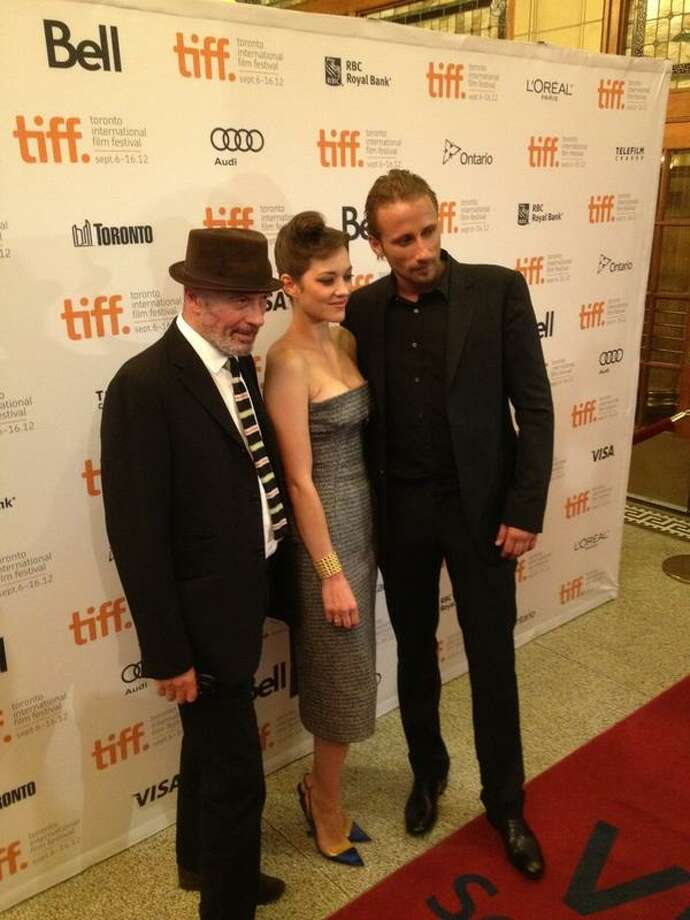 "The stars of ""Rust and Bone"" walk the red carpet at the movie's premiere in Toronto. From left are Jacques Audiard, Marion Cotillard and Matthias Schoenaerts. (Paul Grondahl/Times Union)"