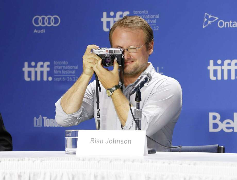 "Writer-director Rian Johnson uses his camera during a photo call and press conference for the film ""Looper"" during the 2012 Toronto International Film Festival at the TIFF Bell Lightbox on Thursday, Sept. 6, 2012 in Toronto. Photo: Todd Williamson, TODD WILLIAMSON/INVISION/AP / Invision"