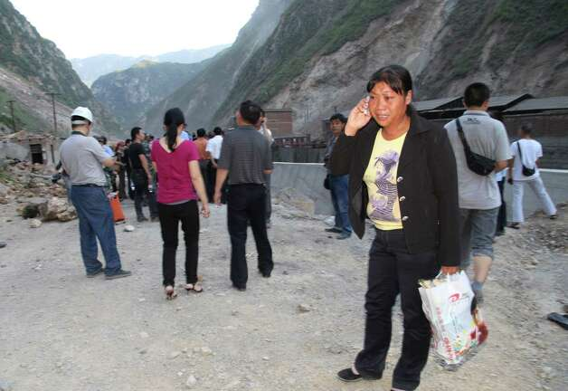 A woman cries while she makes a phone call on a blocked road in Yiliang, southwest China's Yunnan province on Friday following two shallow earthquakes in  the remote and mountainous border area of Yunnan and Guizhou province of southwest China.  Dozens of people were killed and 550 injured when two shallow quakes with a magnitude of both at 5.6 struck a remote and mountainous area of southwest China, toppling buildings and sparking chaos in the streets, officials said. ( AFP/AFP/GettyImages) Photo: AFP, Ap/getty / 2012 AFP