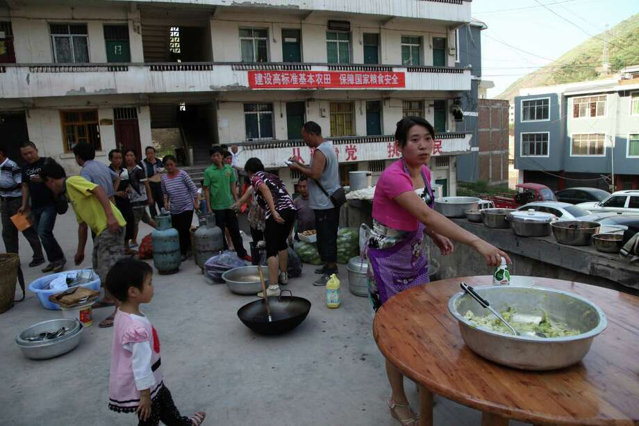 Residents gather to cook a meal in Yiliang, southwest China's Yunnan province on Friday, following two shallow quakes that struck the remote and mountainous border area of Yunnan and Guizhou province of southwest China.   Dozen of people were killed and 550 injured when two shallow quakes with a magnitude of both at 5.6 struck a remote and mountainous area of southwest China, toppling buildings and sparking chaos in the streets, officials said.    ( AFP/AFP/GettyImages) Photo: AFP, Ap/getty / 2012 AFP