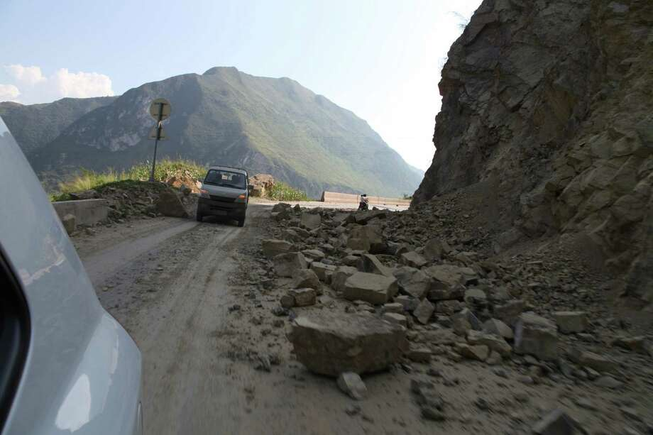 Vehicles make their way slowly along the road after a rock-fall in Yiliang, southwest China's Yunnan province on Friday after two shallow earthquakes hit the remote and mountainous border area of Yunnan and Guizhou province of southwest China.   Dozens of people were killed and 550 injured when two shallow quakes with a magnitude of both at 5.6 struck a remote and mountainous area of southwest China, toppling buildings and sparking chaos in the streets, officials said.   ( AFP/AFP/GettyImages) Photo: AFP, Ap/getty / 2012 AFP