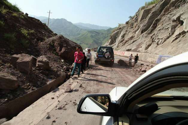 Vehicles make their way slowly along the road after a rock-fall in Yiliang, southwest China's Yunnan province on Friday following two shallow quakes that struck the remote and mountainous border area of Yunnan and Guizhou province of southwest China.   Dozens of people were killed and 550 injured when two shallow quakes with a magnitude of both at 5.6 struck a remote and mountainous area of southwest China, toppling buildings and sparking chaos in the streets, officials said.      ( AFP/AFP/GettyImages) Photo: AFP, Ap/getty / 2012 AFP
