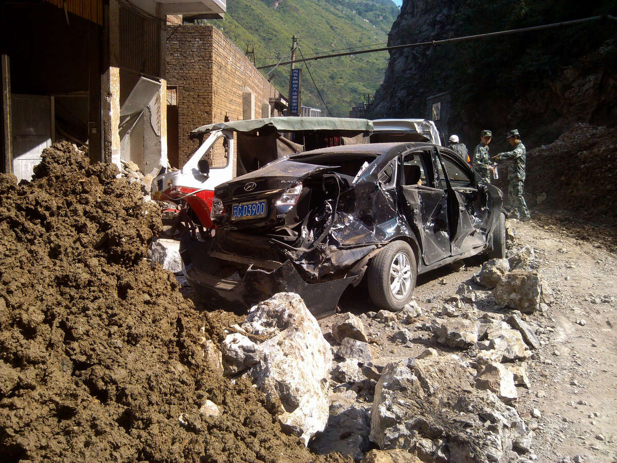 In this photo provided by China's Xinhua News Agency, damaged cars are seen in Luozehe town, Yiliang County, southwest China's Yunnan Province, Friday. A series of earthquakes collapsed houses and triggered landslides in a remote mountainous part of southwestern China on Friday, killing dozens of people with the toll expected to rise. Damage was preventing rescuers from reaching some outlying areas, and communications were disrupted. (AP Photo/Xinhua, Zhou Hongpeng)