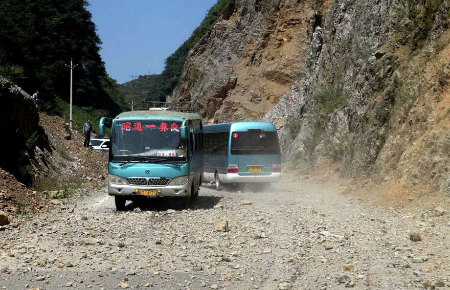 In this photo provided by China's Xinhua News Agency, buses encoutner the rockfall triggered by an earthquake in Yiliang County, southwest China's Yunnan Province, Friday. A series of earthquakes collapsed houses and triggered landslides in a remote mountainous part of southwestern China on Friday, killing at least 50 people with the toll expected to rise. Damage was preventing rescuers from reaching some outlying areas, and communications were disrupted. (AP Photo/Xinhua, Zhang Guangyu) Photo: Ap/getty