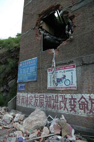 A damaged building in Yiliang, southwest China's Yunnan province on Friday after two shallow quakes that struck the remote and mountainous border area of Yunnan and Guizhou province of southwest China.   Dozens of people were killed and 550 injured when two shallow quakes with a magnitude of both at 5.6 struck a remote and mountainous area of southwest China, toppling buildings and sparking chaos in the streets, officials said.   ( AFP/AFP/GettyImages) Photo: AFP, Ap/getty / 2012 AFP