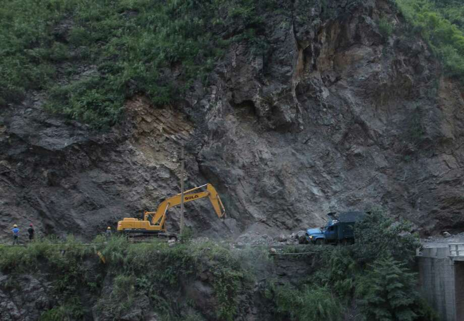 An excavator clears a road after a rock-fall in Yiliang, southwest China's Yunnan province on Friday, following two shallow quakes that struck the remote and mountainous border area of Yunnan and Guizhou province of southwest China.  Dozens of people were killed and 550 injured when two shallow quakes with a magnitude of both at 5.6 struck a remote and mountainous area of southwest China, toppling buildings and sparking chaos in the streets, officials said.  ( AFP/AFP/GettyImages) Photo: AFP, Ap/getty / 2012 AFP