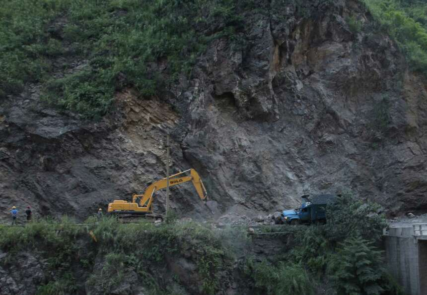 An excavator clears a road after a rock-fall in Yiliang, southwest China's Yunnan province on Friday