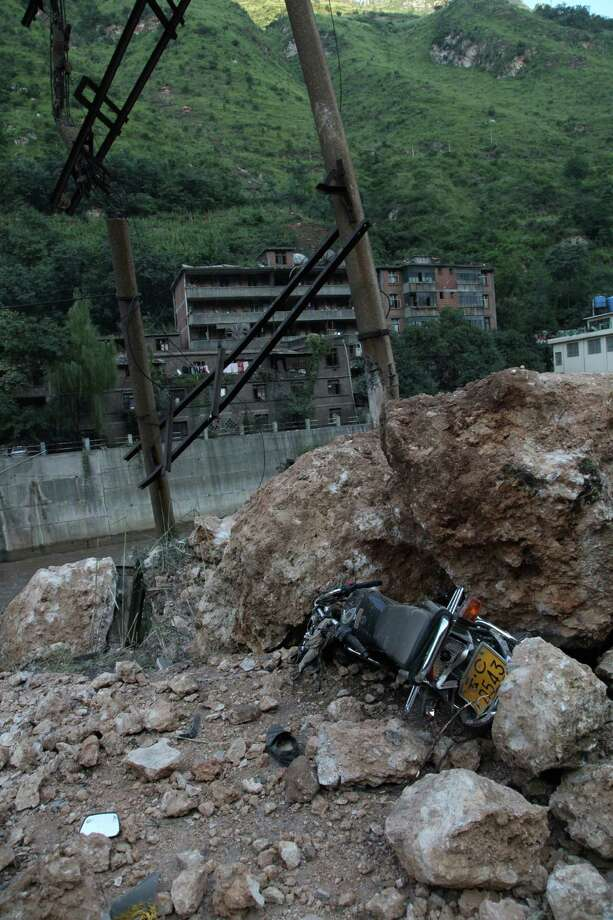 A motorbike lies buried under fallen rocks in Yiliang, southwest China's Yunnan province on Friday, after two shallow quakes struck the remote and mountainous border area of Yunnan and Guizhou province of southwest China.  Dozens of people ere killed and 550 injured when two shallow quakes with a magnitude of both at 5.6 struck a remote and mountainous area of southwest China, toppling buildings and sparking chaos in the streets, officials said. (AFP/AFP/GettyImages) Photo: AFP, Ap/getty / 2012 AFP