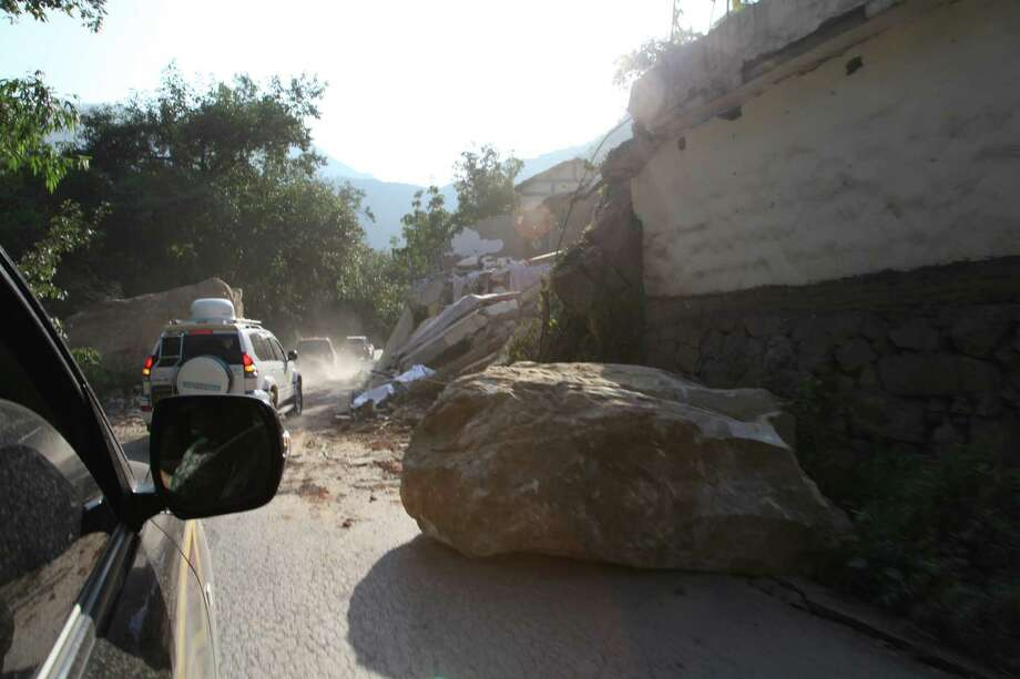 A boulder lies on a road in Yiliang, southwest China's Yunnan province on Friday following two shallow quakes that struck the remote and mountainous border area of Yunnan and Guizhou province of southwest China.   Dozens of people were killed and 550 injured when two shallow quakes with a magnitude of both at 5.6 struck a remote and mountainous area of southwest China, toppling buildings and sparking chaos in the streets, officials said. (Photo credit should read AFP/AFP/GettyImages) Photo: AFP, Ap/getty / 2012 AFP
