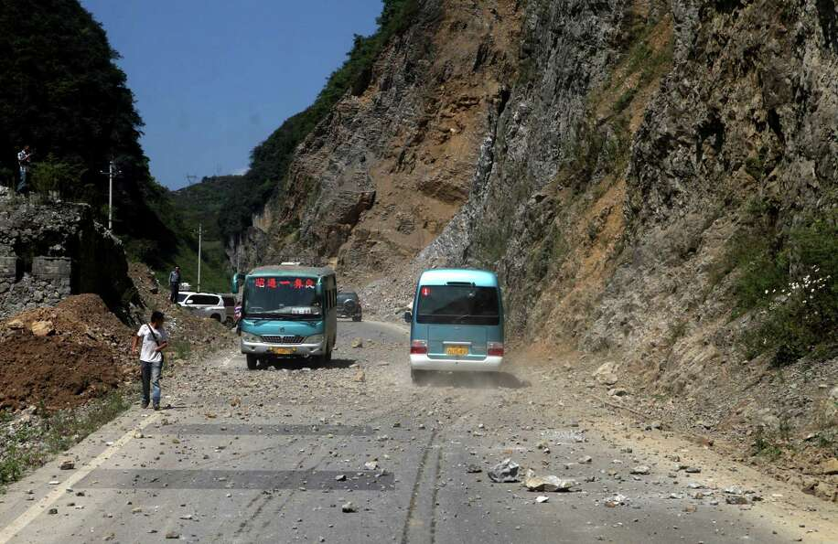 Two buses make their way across a road full of fallen rocks after a series of earthquakes, one of th
