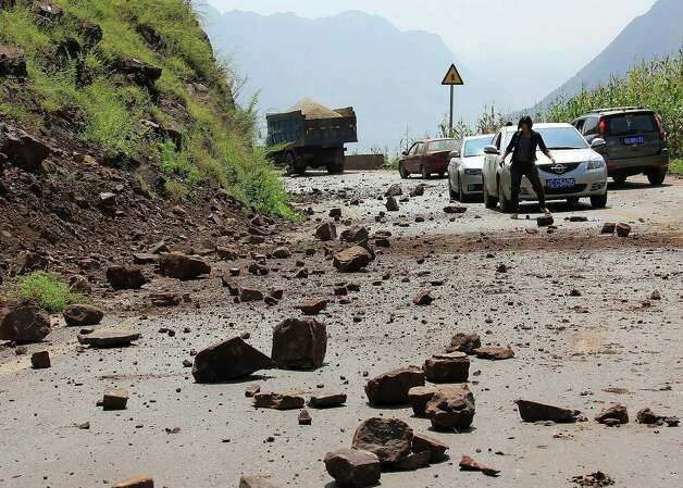 A woman tries to clear the fallen rocks from the mountain on a road near Zhaotong town, Yiliang County, southwest China's Yunnan Province, Friday. A series of earthquakes collapsed houses and triggered landslides Friday in a remote mountainous part of southwestern China where damage was preventing rescues and communications were disrupted. At least 64 deaths have been reported. (AP Photo) Photo: Associated Press