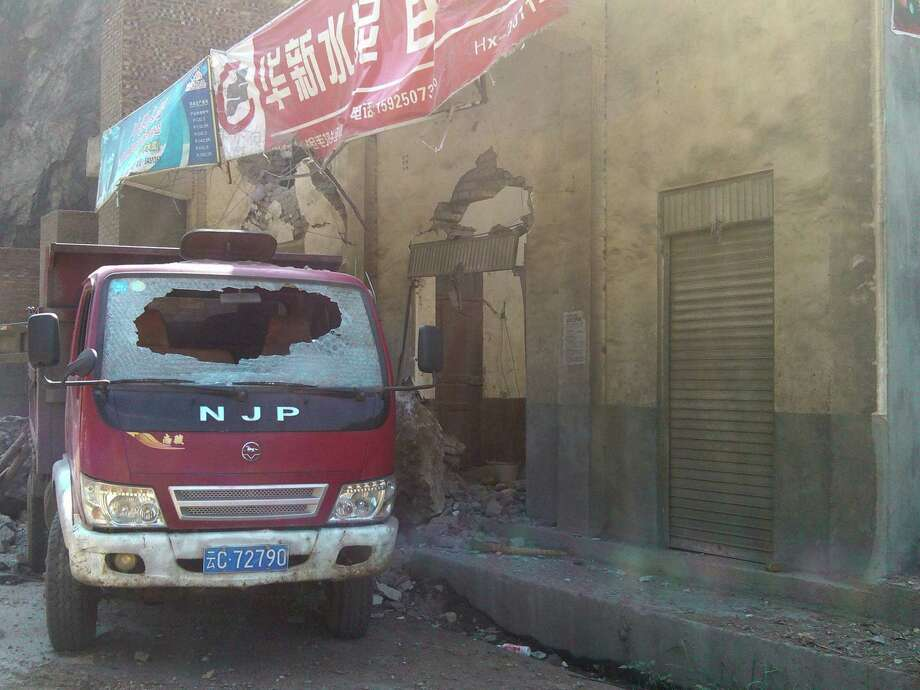 In this photo provided by Xinhua News Agency, a damaged truck parks by damaged houses in Luozehe Town, Yiliang County, southwest China's Yunnan Province on Friday. A series of earthquakes collapsed houses and triggered landslides in a remote mountainous part of southwestern China on Friday, killing dozens of people with the toll expected to rise. Damage was preventing rescuers from reaching some outlying areas, and communications were disrupted. (AP Photo/Xinhua, Zhou Hongpeng) Photo: Associated Press