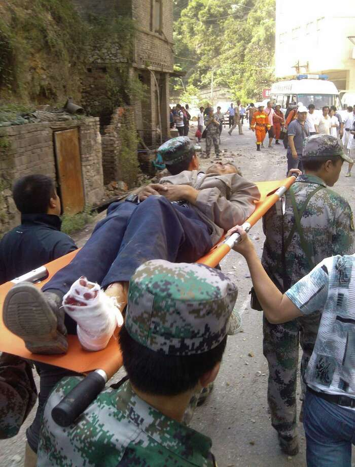 In this photo provided by Xinhua News Agency, an injured villager is carried on a stretcher by rescuers following an earthquake in Luozehe Town, Yiliang County, southwest China's Yunnan Province, Friday. A series of earthquakes collapsed houses and triggered landslides in a remote mountainous part of southwestern China on Friday, killing dozens of people with the toll expected to rise. Damage was preventing rescuers from reaching some outlying areas, and communications were disrupted. (AP Photo/Xinhua, Zhou Hongpeng) Photo: Associated Press