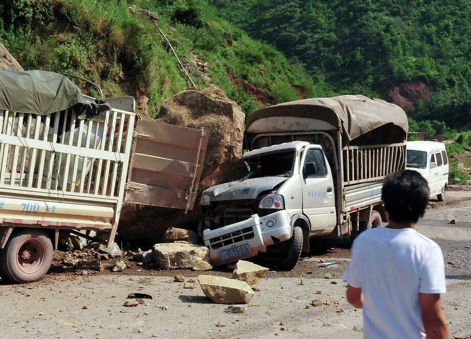 A man looks at the trucks damaged by fallen rocks after an  earthquake in Zhaotong town, Yiliang County, southwest China's Yunnan Province, Friday. A series of earthquakes collapsed houses and triggered landslides Friday in a remote mountainous part of southwestern China where damage was preventing rescues and communications were disrupted. At least 64 deaths have been reported. (AP Photo) Photo: Associated Press