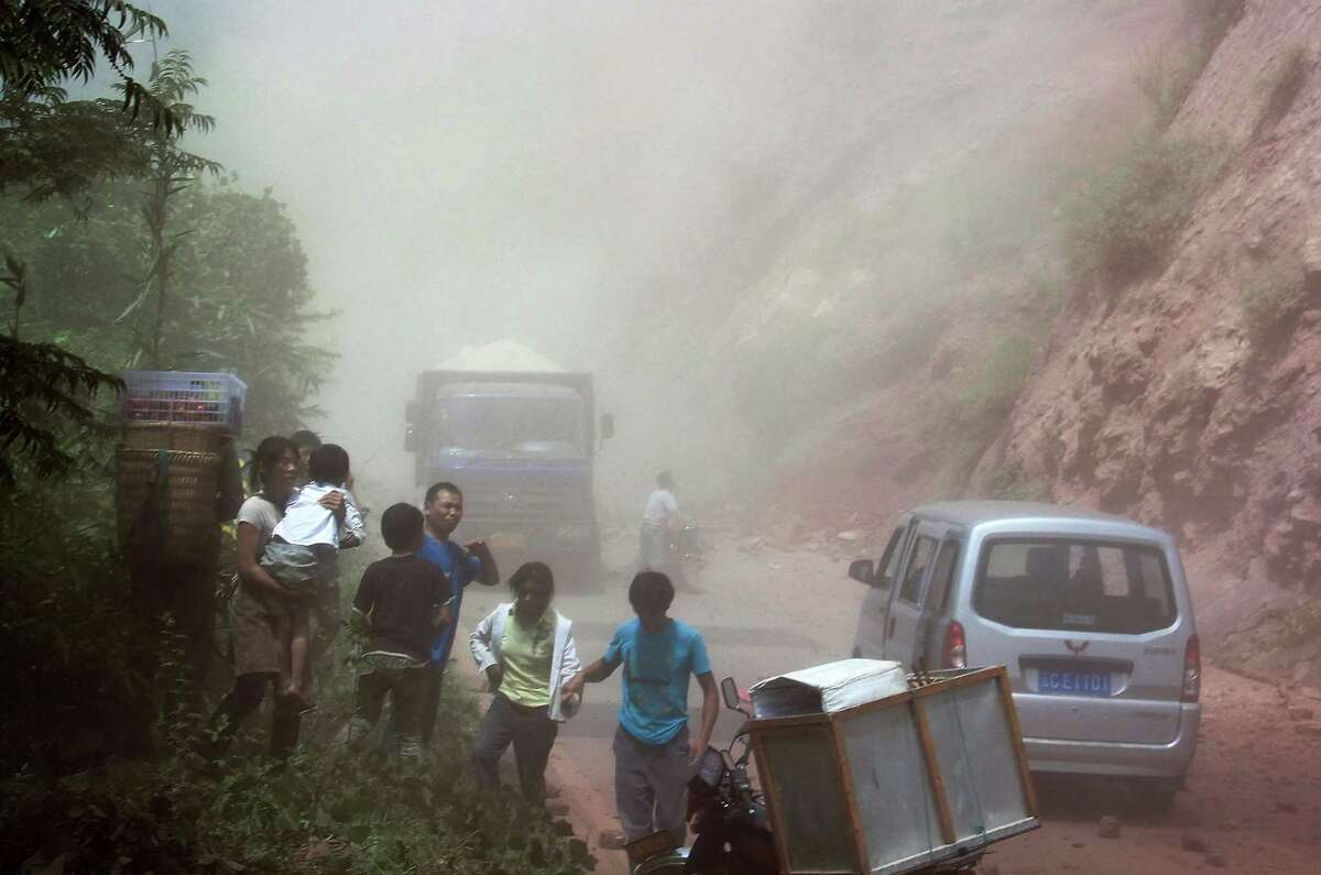 People run as rocks fall near their vehicles after the area was hit by an earthquake in Zhaotong town, Yiliang County, southwest China's Yunnan Province, Friday. A series of earthquakes collapsed houses and triggered landslides Friday in a remote mountainous part of southwestern China where damage was preventing rescues and communications were disrupted. Dozens of deaths have been reported. (AP Photo)