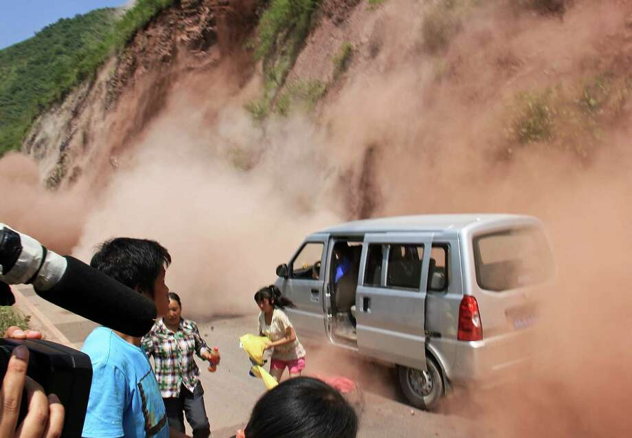 People run as fallen rocks land near their vehicle after the area was hit by earthquake in Zhaotong town, Yiliang County, southwest China's Yunnan Province, Friday, Sept. 7, 2012. A series of earthquakes collapsed houses and triggered landslides Friday in a remote mountainous part of southwestern China where damage was preventing rescues and communications were disrupted. At least 64 deaths have been reported. (AP Photo) CHINA OUT Photo: Associated Press