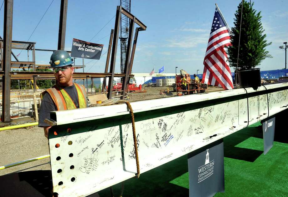 """Steelworker James Moonen guides the signed final steel beam into the air during a """"topping-off"""" ceremony for the Visual and Performing Arts Center at Western Connecticut State University's westside campus in Danbury Friday, Sept. 7, 2012. Photo: Michael Duffy / The News-Times"""
