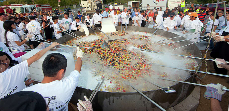 This Monday photo released by the University of Massachusetts in Amherst, Mass., shows a seafood stew cooking at a Labor Day barbecue to celebrate the return of students to the campus. Chefs at the university set a new Guinness World Record by cooking the 6,656-pound seafood stew in the same custom-built, 1-ton, 14-foot frying pan used last year to set a Guinness Record of 4,010 pounds for the world's largest stir-fry.  (AP Photo/University of Massachusetts Amherst, John Solem) Photo: Ap/getty
