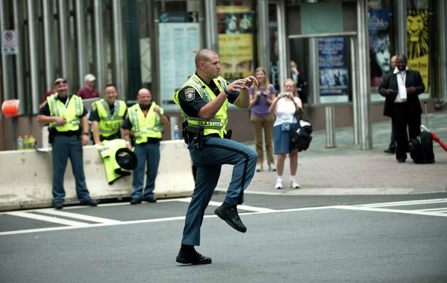A sheriff's deputy puts a bit of creativity into directing traffic as people arrive for the second day of the 2012 Democratic National Convention at the Time Warner Arena on Tuesday in Charlotte, N.C.         ( BRENDAN SMIALOWSKI/AFP/GettyImages) Photo: BRENDAN SMIALOWSKI, Ap/getty / 2012 AFP