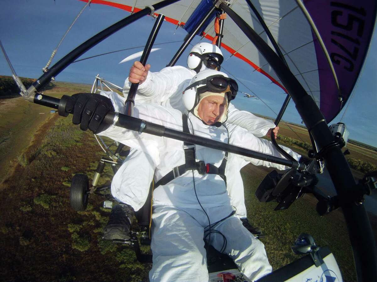 Russian President Vladimir Putin pilots a motorized hang glider while flying with cranes as he takes part in a scientific experiment as part of the