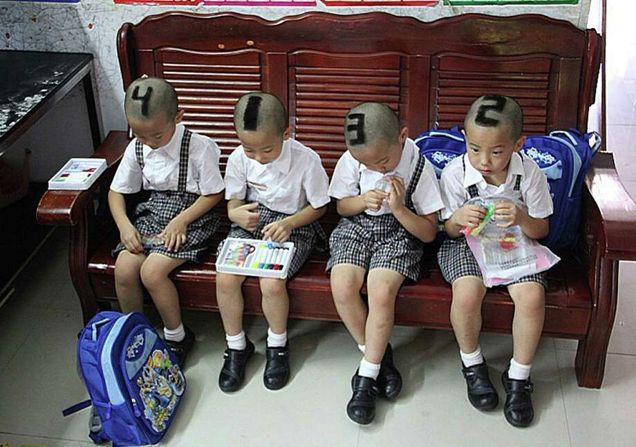 This picture taken on Monday shows 6-year-old quadruplets from Shenzhen, south China's Guangdong Province with their hair shaved into various numbers before they start go to school for their first time. Their parents decided to mark them with 1, 2, 3, 4 on their heads to make it easier for teachers and classmates to tell them apart.  (STR/AFP/GettyImages) Photo: AFP, Ap/getty / 2012 AFP