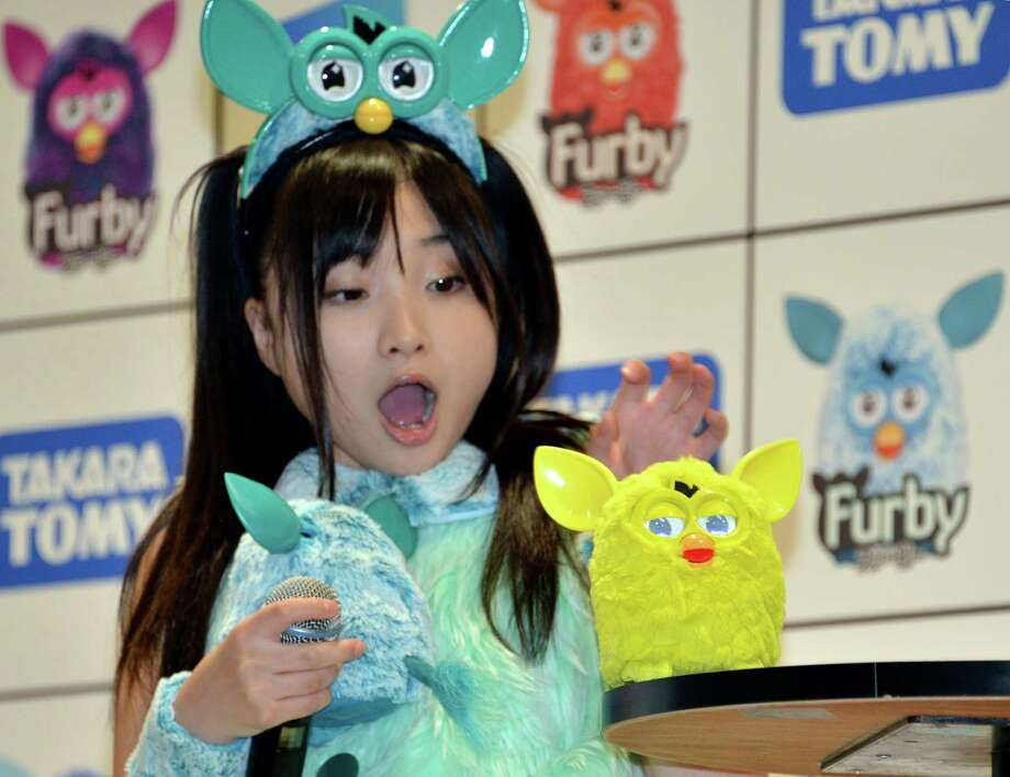 "A young women displays the new electronic robot toy called ""Furby"", produced by US toy giant Hasbro and distributed by Japanese toy maker Tomy, at a press preview in Tokyo on Tuesday.  Furby, who debuted in 1981 and sold over 40 million units in the world, has been renewed and will begin to be sold in Japan from next month. The user can use an iPhone or iPad to take care of the new Furby, such as feeding and communication with the robot pet         (YOSHIKAZU TSUNO/AFP/GettyImages) Photo: YOSHIKAZU TSUNO, Ap/getty / 2012 AFP"