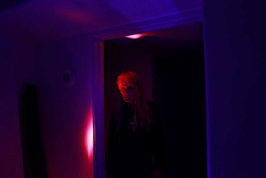 With black lights blazing, Goth Girl stands in her dimly hallway in San Francisco, Calif. Photo: Mike Kepka, The Chronicle