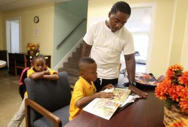 Jerald Adams Jr. helps his son, Ja'vari Hamilton, 6, with reading a book while daughter, Jeriyah Adams, 6, waits her turn to read at The Children's Center, Tuesday, Sept. 4, 2012, in Galveston. The children are part of a group of about 700 children who meet the federal definition for homelessness going to school in Galveston. (HC)