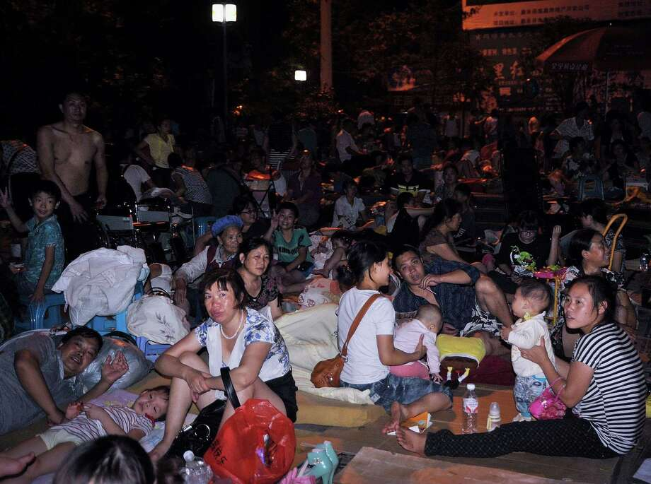 People gather at a square following an earthquake in Zhaotong town, Yiliang County, southwest China's Yunnan Province on Friday. A series of earthquakes collapsed houses and triggered landslides Friday in a remote mountainous part of southwestern China where damage was preventing rescues and communications were disrupted. At least 64 deaths have been reported. (AP Photo) Photo: Associated Press
