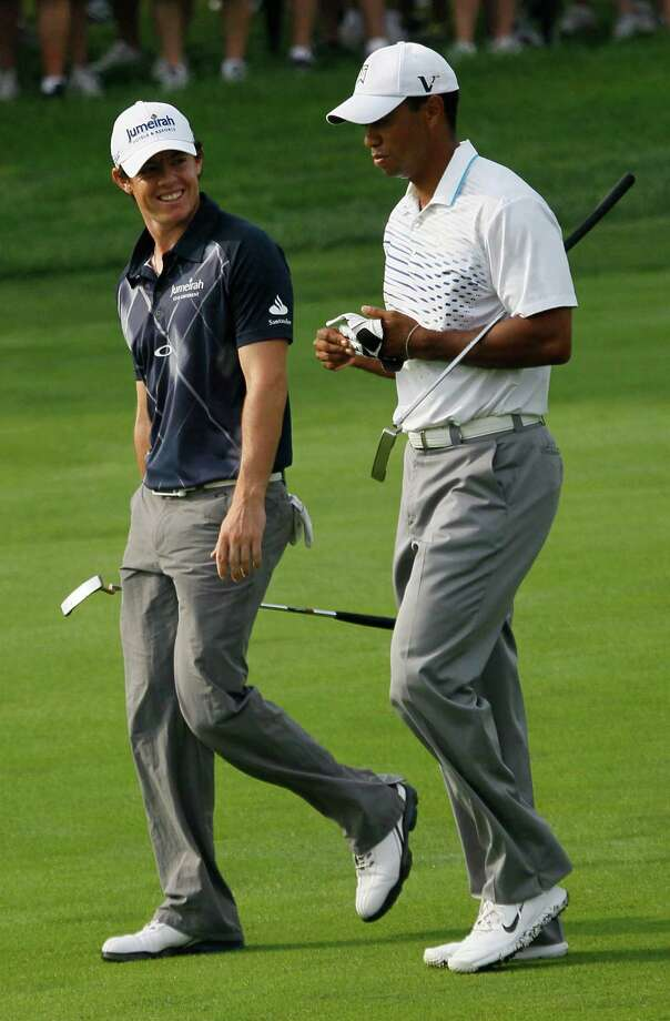 Rory McIlroy of Northern Ireland, left,  smiles at Tiger Woods on the second fairway during the second round of the BMW Championship PGA golf tournament at Crooked Stick Golf Club in Carmel, Ind., Friday, Sept. 7, 2012. (AP Photo/Charles Rex Arbogast) Photo: Charles Rex Arbogast, Associated Press / AP