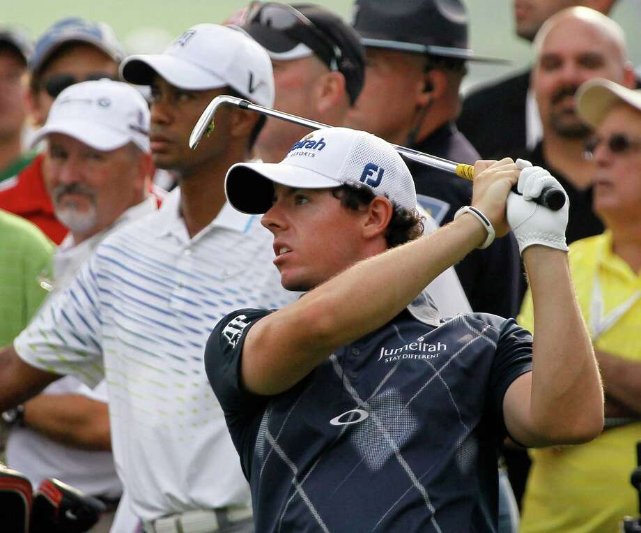 Rory McIlroy of Northern Ireland, tees off on the third hole as Tiger Woods looks on, during the second round of the BMW Championship PGA golf tournament at Crooked Stick Golf Club in Carmel, Ind., Friday, Sept. 7, 2012. (AP Photo/Charles Rex Arbogast) Photo: Charles Rex Arbogast, Associated Press / AP