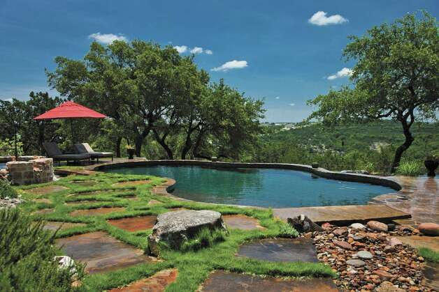 "Grass softens a deck of Oklahoma flagstone around a Hill Country pool designed by Mike Logsdon of Land Design. Below, perforated metal columns add interest to a courtyard in a house in the Lavaca neighborhood, says designer Alberto Isunza. Both are featured in ""Spectacular Outdoor Living: Texas,"" by Jolie Carpenter. Photo: Jon King Keisling / © Copyright 2010 Jon King Keisling"