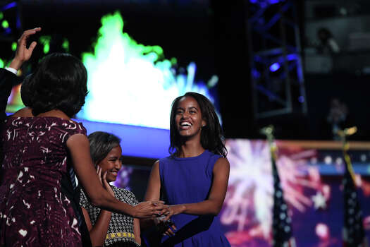Malia Obama, right, her sister, Sasha, and their mother, First Lady Michelle Obama, take the spotlight on stage after President Barack Obama's speech to conclude the Democratic National Convention at Time Warner Cable Arena in Charlotte, NC on Thursday, Sept. 6, 2012. Photo: Lisa Krantz, San Antonio Express-News / San Antonio Express-News