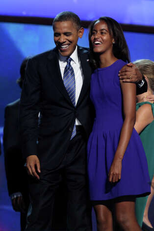 Malia Obama, right, shares a laugh with her father, President Barack Obama, on stage after the President'