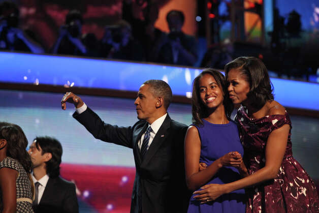 First Lady Michelle Obama embraces her daughter Malia as President Barack Obama waves to supporters at the conclusion of the Democratic National Convention at Time Warner Cable Arena in Charlotte, NC on Thursday, Sept. 6, 2012. Photo: Lisa Krantz, San Antonio Express-News / San Antonio Express-News