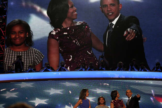 President Barack Obama, with his wife, Michelle Obama, and daughters, Malia, far left, and Sasha take the spotlight on stage at the conclusion of the Democratic National Convention at Time Warner Cable Arena in Charlotte, NC on Thursday, Sept. 6, 2012. Photo: Lisa Krantz, San Antonio Express-News / San Antonio Express-News