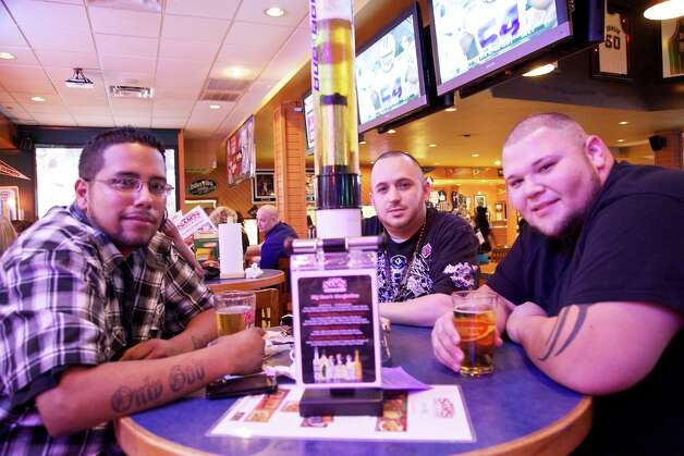 Adrian Arreola, Joshua Gomez, and Timothy Zendejas are enjoying a tall beer at Big Sam's grill and bar. Photo: Xelina Flores-Chasnoff, For The Express-News