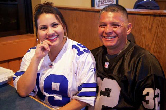 Diane Martinez and Carlos Ancira are enjoying game night at Big Sam's, even though they are rooting for different teams. Photo: Xelina Flores-Chasnoff, For The Express-News