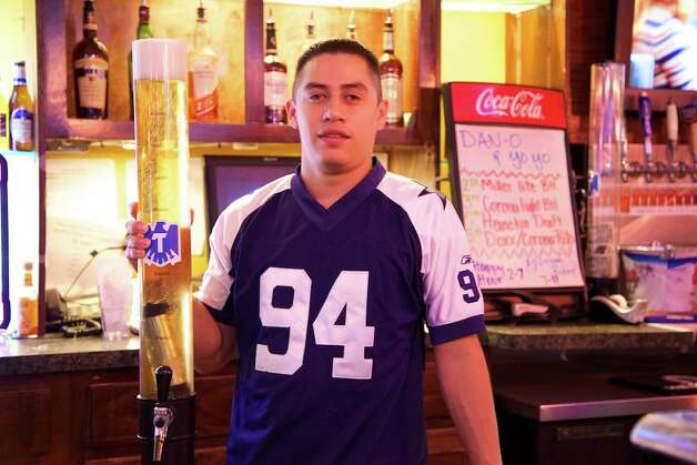 Daniel Duran is serving extra tall beers at Big Sam's grill and bar. Photo: Xelina Flores-Chasnoff, For The Express-News