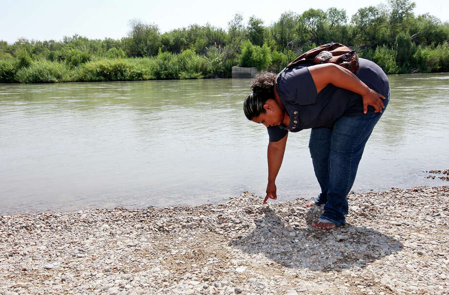 Nora Isabel Lam Gallegos points to what she says is blood at the site where her husband, Guillermo Arévalo Pedroza, was shot on the Mexican side of the Rio Grande. Her family had gone to a park there for a birthday celebration. Photo: Edward A. Ornelas, San Antonio Express-News / © 2012 San Antonio Express-News