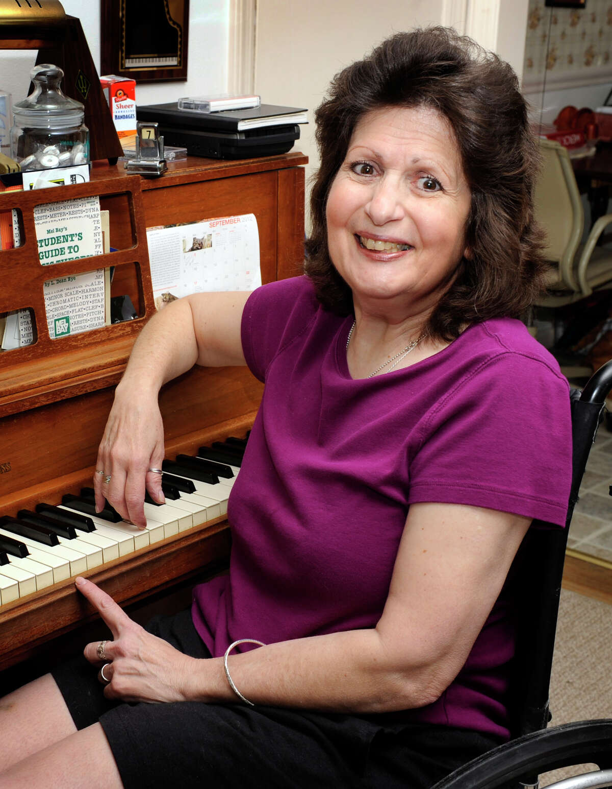 Piano teacher Bonnie Peterson, 57, sits at her piano at home in Brookfield, Friday, Sept. 7, 2012.